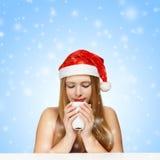 Schöne junge Frau in Weihnachtsmann-Hut, der am Tabellenesprit stationiert Lizenzfreies Stockbild