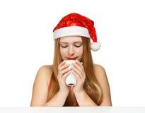 Schöne junge Frau in Weihnachtsmann-Hut, der am Tabellenesprit stationiert Lizenzfreie Stockbilder