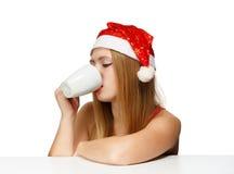 Schöne junge Frau in Weihnachtsmann-Hut, der am Tabellenesprit stationiert Stockfoto