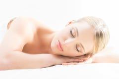 Schöne junge Frau, welche die Freizeit liegt in einer Matte im Badekurort hat Lizenzfreies Stockfoto