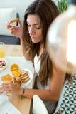 Schöne junge Frau, welche die Nachrichten liest und Frühstück genießt Stockbild