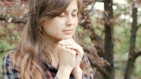 Schöne junge Frau wendet sich an Gott mit Gefühlen im Gebet, faltete das Mädchen ihre Arme an ihrem Kasten und mit Dankbarkeitsbl stock video footage