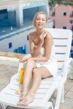 Schöne junge Frau wickelte das weiße Tuch ein, das auf Sonnenbett-APP sitzt lizenzfreie stockfotos