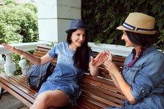 Schöne junge Frau zwei, die auf einer Bank im Park stillsteht lizenzfreie stockbilder