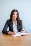 Schöne junge Frauen benutzt ein intelligentes Telefon und macht Anmerkungen beim Sitzen am Schreibtisch lizenzfreies stockbild