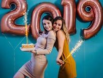 Schöne junge Frauen des guten Rutsch ins Neue Jahr und der frohen Weihnachten, die mit Kuchen und brennenden Kerzen feiern lizenzfreie stockfotos