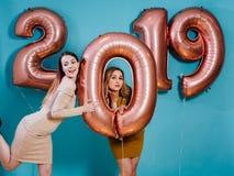 Schöne junge Frauen des guten Rutsch ins Neue Jahr und der frohen Weihnachten mit Ballonen lizenzfreies stockbild