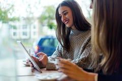 Schöne junge Frauen, die digitale Tablette in der Kaffeestube verwenden Lizenzfreie Stockfotos
