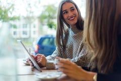 Schöne junge Frauen, die digitale Tablette in der Kaffeestube verwenden Lizenzfreies Stockfoto