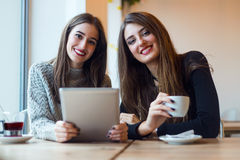 Schöne junge Frauen, die digitale Tablette in der Kaffeestube verwenden Stockfotos