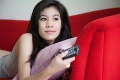 Schöne junge Frauen, die Fernfernsehen auf rotem Sofa halten stockbilder