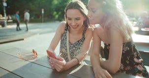 Schöne junge Frauen, die Fotos an einem Handy aufpassen Lizenzfreies Stockbild
