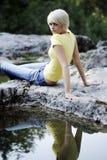 Schöne junge Frauen, die nahe einem Felsenpool sich entspannen Lizenzfreies Stockbild
