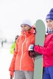 Schöne junge Frauen mit dem Snowboard, der weg schaut Lizenzfreie Stockfotos