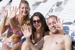 Schöne junge Freunde, die Spaß auf dem Pool haben Lizenzfreie Stockbilder