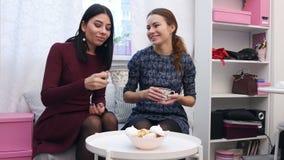 Schöne junge Freundinnen, die Tee im Kleidungsausstellungsraum nach dem Einkaufen trinken stock video