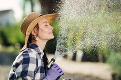 Schöne junge Gärtnerfrau, die Spaß bei der Bewässerung des Gartens im heißen Sommertag hat stockfoto