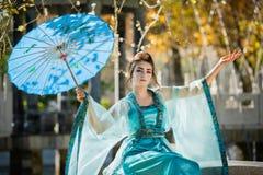 Schöne junge Geisha mit einem blauen Regenschirm Stockfotografie