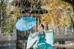Schöne junge Geisha mit einem blauen Regenschirm Lizenzfreies Stockfoto