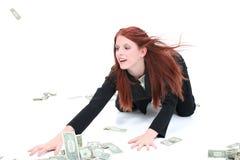 Schöne junge Geschäftsfrau auf dem Fußboden, der herauf Bargeld ergreift lizenzfreies stockbild