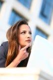 Schöne junge Geschäftsfrau auf dem Laptopdenken Stockbilder