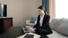 Schöne junge Geschäftsfrau, die an Computer in einem presidetial Klagenraum des Hotels arbeitet stock video footage