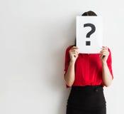 Schöne junge Geschäftsfrau, die ein Fragezeichen hält Lizenzfreies Stockfoto