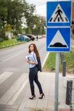 Schöne junge Geschäftsfrau, die eine Straße auf einem Fußgänger kreuzt lizenzfreie stockfotos