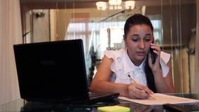 Schöne junge Geschäftsfrau, die an einem Handy bespricht ein Geschäftsprojekt in einem Büro sitzt an einem Tisch spricht stock video