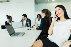 Schöne junge Geschäftsfrau, die lächelt und glücklich während spricht Lizenzfreie Stockbilder