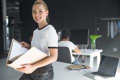 schöne junge Geschäftsfrau, die Ordner mit Dokumenten hält und an der Kamera lächelt Stockbilder