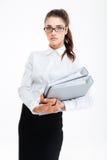 Schöne junge Geschäftsfrau, die Ordner mit Dokumenten steht und hält Stockfotografie