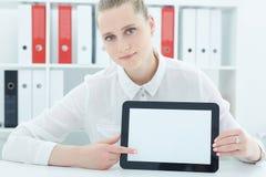 Schöne junge Geschäftsfrau, die Tablette in den Händen sitzen im Büro hält Lizenzfreie Stockfotos