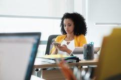 Schöne junge Geschäftsfrau mit Handy im Planungs- und Führungsstab lizenzfreie stockbilder