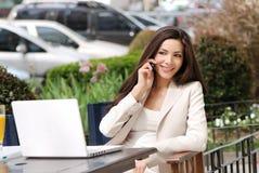 Schöne junge Geschäftsfrau mit movil Stockfotos
