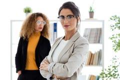 Schöne junge Geschäftsfrau zwei, die im Büro aufwirft Stockfotografie