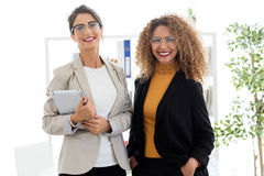 Schöne junge Geschäftsfrau zwei, die im Büro aufwirft Lizenzfreies Stockbild