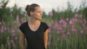 Schöne junge gesunde Frau, die an einem grünen Feld steht und weg schaut stock video footage