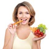 Schöne junge gesunde Frau, die einen Salat isst. Stockbild