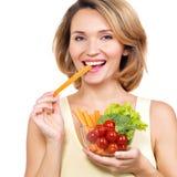Schöne junge gesunde Frau, die einen Salat isst Lizenzfreie Stockfotos