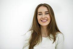 Schöne junge glückliche Frau, die gegen eine weiße Wand aufwirft Lizenzfreie Stockbilder