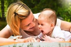 Schöne junge glückliche Mutter mit dem blonden Haar, das auf die Decke legt und mit ihrem neugeborenen Baby spielt lizenzfreie stockbilder