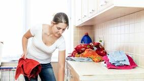 Schöne junge Hausfrau, die Hausarbeit in der Waschküche tut stockbild