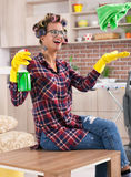 Schöne junge Hausfrau mit dem Lockenwickler, der Hausaufgaben tut Lizenzfreie Stockfotos