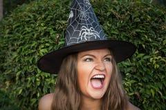Schöne junge Hexe im schwarzen Hut schreiend Lizenzfreies Stockfoto