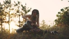 Schöne junge Hippiefrau mit den Dreadlocks, die auf djembe spielen Flippige Frau, die in der Natur auf einer ethnischen Trommel a stock video footage
