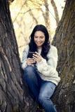 Schöne junge hispanische, indianische, ethnisch gemischte Frau mit Handy stockbild