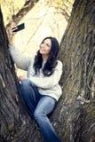Schöne junge hispanische, indianische, ethnisch gemischte Frau mit Handy stockfoto