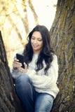 Schöne junge hispanische, indianische, ethnisch gemischte Frau mit Handy stockfotografie