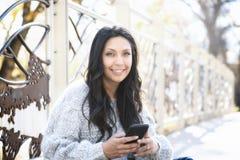 Schöne junge hispanische, indianische, ethnisch gemischte Frau mit Handy lizenzfreies stockfoto
